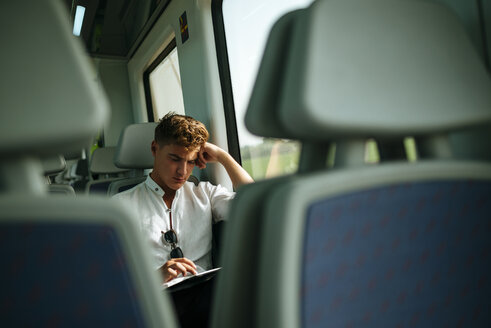 Young man using a tablet on a train - KIJF000547