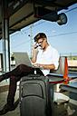 Young man using a laptop at station platform - KIJF000556