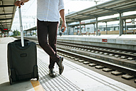 Man with suitcase waiting at station platform - KIJF000562