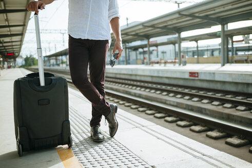 Man with suitcase waiting at station platform - KIJF000562