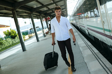 Young man with suitcase walking at station platform - KIJF000565