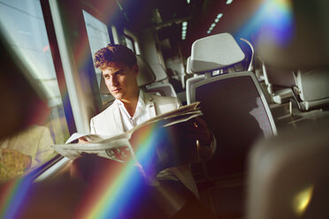 Young man reading a newspaper on a train - KIJF000568