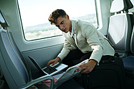 Young man using a laptop on a train - KIJF000571