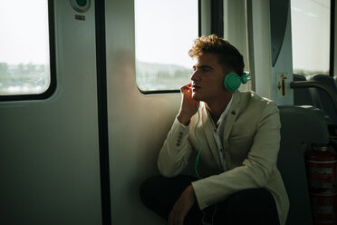 Young man listening to music on a train - KIJF000574