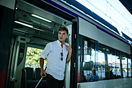 Young man leaving the train at a station - KIJF000577