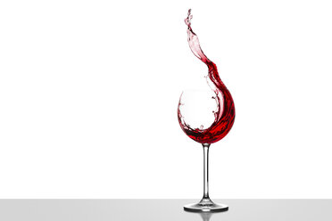 Red wine splashing in glass in front of white background - CPF000031