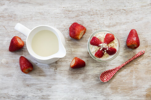 Glass of overnight oats with strawberries and milk jug on wood - EVGF003019