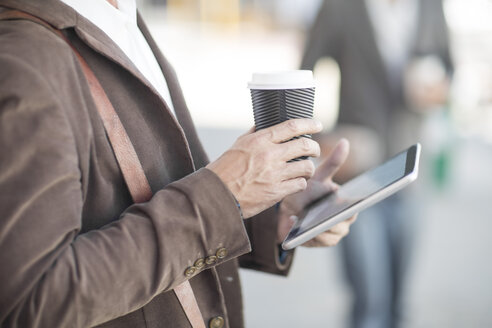 Man with digital tablet and coffee to go outdoors - ZEF008982