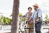 Senior couple with bicycle and wheeled walker - UUF008045