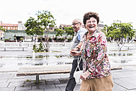 Germany, Mannheim, happy senior couple walking hand in hand - UUF008051