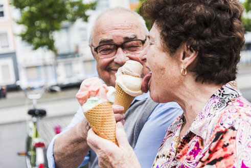 Senior couple enjoy eating ice cream together - UUF008054