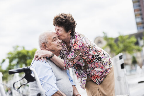 Senior woman kissing her husband - UUF008060