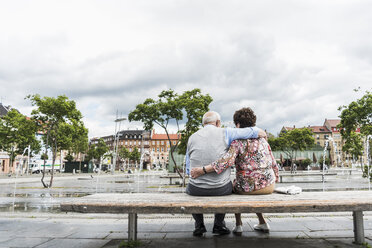 Germany, Mannheim, back view of senior couple sitting on a bench hugging each other - UUF008072