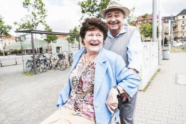 Happy senior couple with wheeled walker - UUF008081