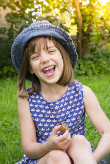 Portrait of laughing little girl sitting on a meadow with gooseberry - LVF005118