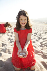 Portrait of smiling little girl kneeling on the beach holding seashells in her hands - VABF000673