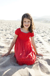Portrait of smiling little girl kneeling on the beach - VABF000676