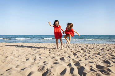 Two little sisters jumping together on the beach - VABF000682