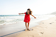 Portrait of happy little girl playing on the beach at seafront - VABF000685