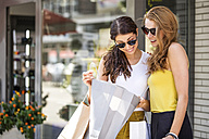 Two happy young women looking into shopping bag - GDF001048
