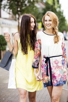 Two happy young women walking in the city - GDF001051