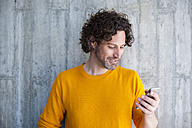 Smiling man with curly brown hair looking on his smartphone - DIGF000577