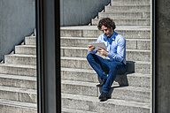 Businessman sitting on stairs looking at tablet - DIGF000583