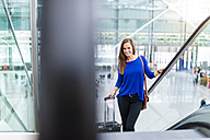 Smiling woman on escalator with suitcase - DIGF000594