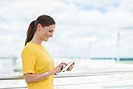 Smiling brunette woman looking at digital tablet - DIGF000603