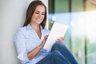 Smiling brunette woman using digital tablet - DIGF000627