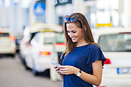 Smiling brunette woman looking at cell phone - DIGF000630