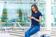 Smiling brunette woman with luggage looking at cell phone - DIGF000633