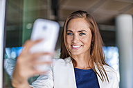 Smiling brunette woman holding cell phone - DIGF000636