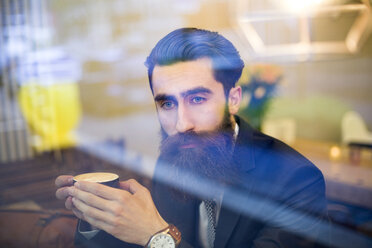 Fashionable man with beard sitting in coffee shop, drinking coffee - NAF000013