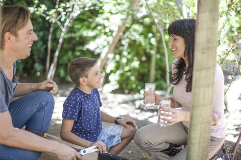 Family in garden with glasses of water - ZEF009006