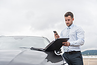 Businessman with documents and cell phone at car - DIGF000644