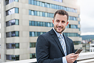 Smiling businessman with cell phone in front of office building - DIGF000653
