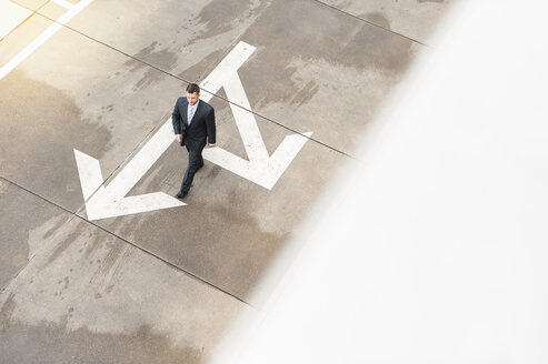 Businessman walking on paving with large arrow - DIGF000662