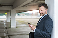 Businessman looking at cell phone in parking garage - DIGF000665