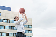 Businessman playing basketball outdoors - DIGF000674