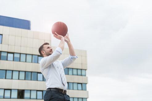Businessman playing basketball outdoors - DIGF000674