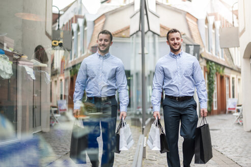 Smiling young man with shopping bags outside a shop - DIGF000680