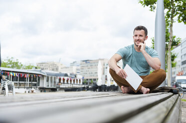 Relaxed young man outdoors sitting on bench with digital tablet - DIGF000704