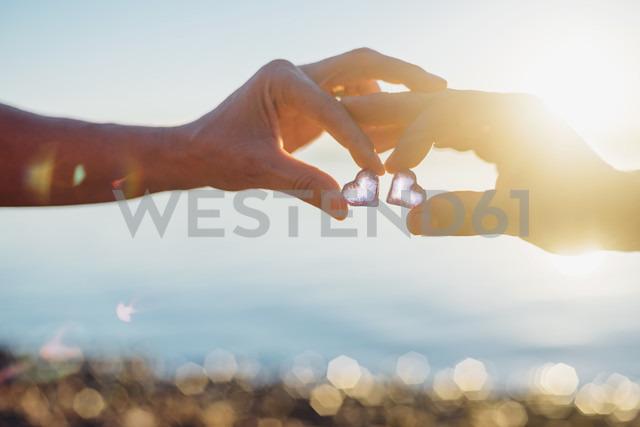 Couple holding glass hearts, against the sun - MJF001997 - Jana Mänz/Westend61