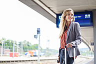 Smiling young woman waiting at platform - DIGF000713