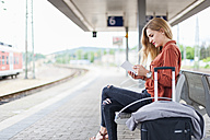 Young woman sitting on bench at platform using tablet - DIGF000716