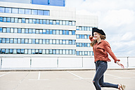 Woman with hat running on roof terrace - DIGF000725