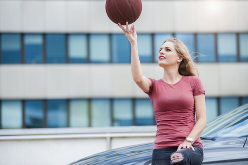 Young woman sitting on car bonnet balancing basketball on her fingers - DIGF000731