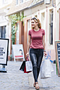 Smiling woman walking on the street carrying shopping bags - DIGF000734