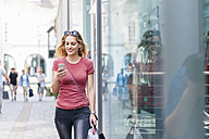 Smiling woman walking on the street with shopping bags looking at her smartphone - DIGF000737